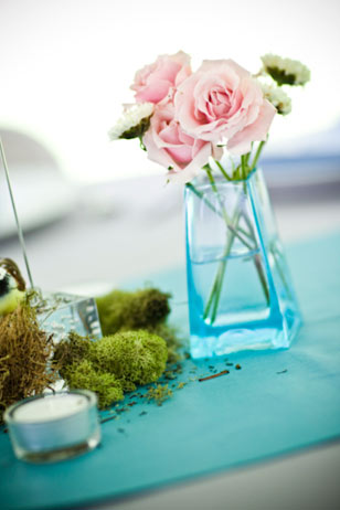 Abby designed her charming centerpieces with vintage vases her mother collected over the course of the year from yard sales and flea markets, accented by Spanish moss. Table runners were made from mismatched shades of $1/yard blue fabric.