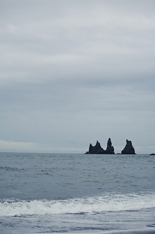 Vik is an Icelandic coastal village, known for its popular offshore spires called Reynisdrangar, meaning 'troll rocks', which are actual columns of black basalt. Legend has it the 'trolls' became petrified by the sun as they were dragging a boat to shore.