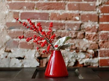 "Red Velvet, $55 This beautiful ""cone"" vase is a hand blown piece made by a local student artist.  It is a beautiful gift item and complimented with red ilex berries and dusty miller."