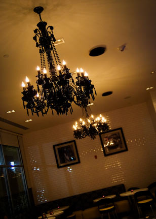 MIXX's whimsical interior plays off a Parisian influence with dramatic, dark red chandeliers, antiqued white wash brick walls, and damask print and butter-colored seating.