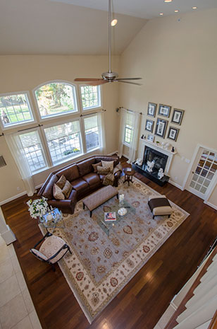 The bright and airy two-story living room where natural light streams through high Palladian windows and there are no solid walls to obstruct the view of the kitchen or dining area.