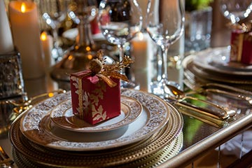 The Music Room will transport guests to Versailles with its ornate and a mirrored dining table set for Christmas Eve dinner.